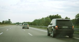 Driver pov on autobahn. GERMANY - CIRCA 2017: Broken Land Rover SUV on the highway emitting smoke during drive stock footage