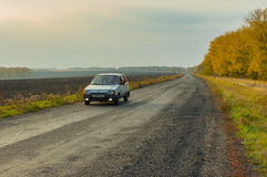 Driver of the private car saluting transport passing by on an autumnal road Royalty Free Stock Image