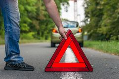 Driver putting out a traffic warning sign Stock Photos