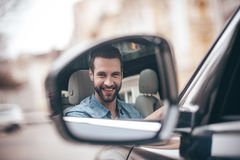 Driver in rear-view mirror. Royalty Free Stock Image
