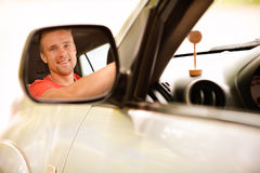 Driver is reflected in mirror. Smiling driver is reflected in mirror of car Stock Photo