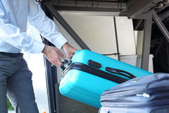 The driver removes luggage. Suitcase in the luggage compartment of the tourist coach Royalty Free Stock Photography