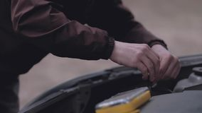 Driver repairing broken car. Driver repairing broken car in outdoor. The car broke down on the road. Unforeseen situation. Close-up. Slowmotion stock video footage