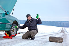 Driver repairing car at the road. Man driver having trouble at a road changing wheel repairing car and giving okay sign hand gesture Stock Photo