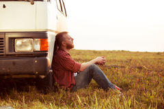 Driver resting in a field near his car. Bearded driver resting in a field near his car Royalty Free Stock Image