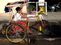A driver rests in his pedal powered tricycle, also known locally as. TACLOBAN CITY, PHILIPPINES - NOVEMBER 9, 2015: A driver rests in his pedal powered tricycle Royalty Free Stock Photography