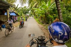 Driver riding his scooter on busy rural road in Nhon Thanh villa royalty free stock photo