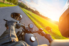 Driver riding motorcycle on an asphalt road stock photo