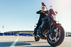 Driver riding motorcycle on empty parking at airport at beautiful autumn time. royalty free stock photography