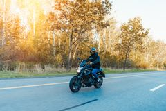 Driver riding motorcycle on empty road in beautiful autumn forest. stock photo