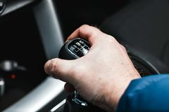Driver`s hand shifting the gear stick. Detail of a driver hand shifting the gear stick Royalty Free Stock Photography