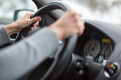 Driver's hands driving a car on a highway. (color toned image; shallow DOF Royalty Free Stock Photography