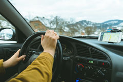 Driver`s hands on a steering wheel and blurred road Stock Photos