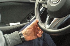 Driver`s hands on the steering wheel of the car. Hands of a driver on steering wheel of a car and empty asphalt road Stock Photography