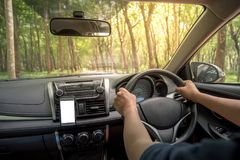 Driver`s hands on the steering wheel inside of a car. With beautiful road in the green forest perspective, road trip travel concepts Royalty Free Stock Photos