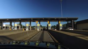 Driver`s Perspective Going Through Tollbooth Plaza. PENNSYLVANIA - Circa September, 2016 - A driver`s perspective heading through the EZ-PASS lane on the stock video