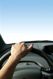 From the Driver's Seat. A blank blue sky is in front of a driver looking out the vehicle's window. This leaves room for text or graphics Stock Photos