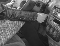 In the driver`s seat of the car, the girl starts the engine, bla. Black and white, the girl behind the wheel of a car turns the ignition key Stock Photo