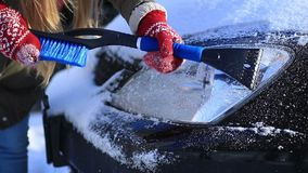 Driver scraping ice from car headlight in winter stock footage