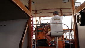 The driver of a sea taxi leads the ship to the coast of Venice. Rear view stock video