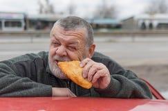 Driver senior affamato che mangia tortino Fotografie Stock