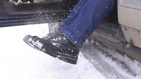 Shake the snow from feet. Driver shaking the snow off her feet stock video footage