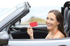 Driver showing a blank credit card in a cabriolet car stock images