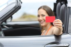 Driver showing a blank credit card in a car on vacation royalty free stock images