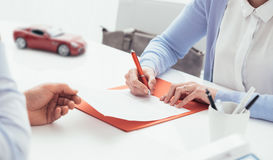Driver signing a car insurance. Woman signing a car insurance policy, the agent is holding the document Royalty Free Stock Photos