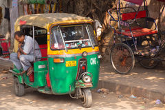 Driver sitting in his tuk-tuk in the street of Delhi, India Stock Images
