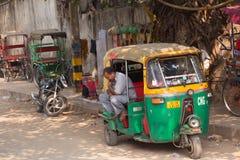 Driver sitting in his tuk-tuk in the street of Delhi, India Royalty Free Stock Photo
