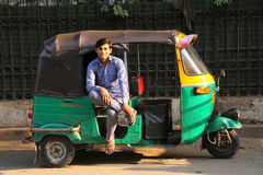 Driver sitting in his tuk-tuk in the street of Delhi, India Royalty Free Stock Images