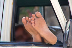 The driver sleeps. Legs sticking out the car window Stock Images