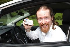 Driver smiling sitting in car with drivers license royalty free stock images