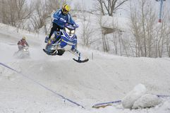Driver on a snowmobile flying down a hill Royalty Free Stock Photography