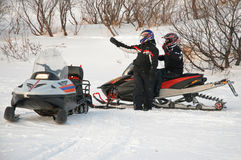 The driver of a snowmobile indicates the way to another friend Royalty Free Stock Image