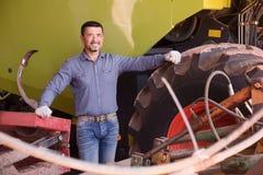 Driver sorridente dell'agricoltore che sta con il grande campo Immagini Stock