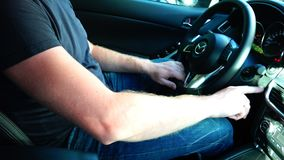 The driver squeezes the brake pedal and presses the engine start button.  stock footage