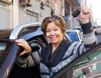 Driver standing with car key. Female driver in golden age standing with car key near automobile Stock Photos