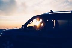 Driver steering car against of sundown Royalty Free Stock Image