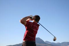 Driver Swing. Golfer shot with a driver against blue sky Royalty Free Stock Photography