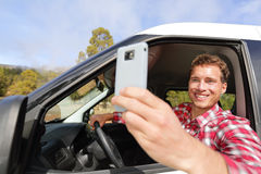 Driver taking photo with camera smartphone driving. In car. Happy man taking picture with smart phone camera out window of car during travel road trip. Young Royalty Free Stock Photos