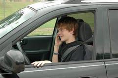 Driver teenager con un telefono delle cellule Fotografia Stock Libera da Diritti