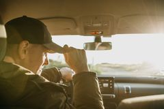 The driver or tourist inside the car adjusts the baseball cap. And waits for someone Stock Images