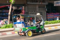 Driver and tourists in tuk-tuk vehicle along the roads of Bangkok, Thailand. The au Stock Photos