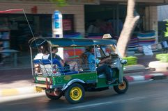 Driver and tourists in tuk-tuk vehicle along the roads of Bangkok, Thailand. The au Royalty Free Stock Image