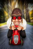 Driver on toy racing car. Man in retro racing hat and goggles driving on toy car at speed with blurred background Royalty Free Stock Images