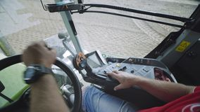 Driver tractor hands steering wheel. Tractor cabin. Agriculture machinery. Driver farming tractor hands on steering wheel during plowing field. View from inside stock video footage