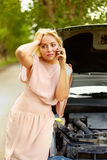 Driver in trouble. Photo of blond woman in trouble standing by her car and talking on cell phone Royalty Free Stock Photos