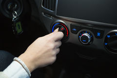 Driver turning car air conditioner knob Stock Photography